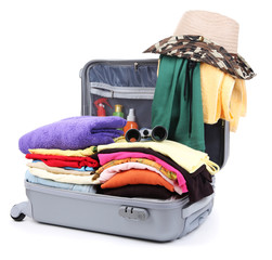Open silver suitcase with clothing isolated on white