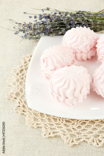 Marshmallows on plate on light background