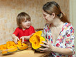Happy mother with girl cooks pumpkin