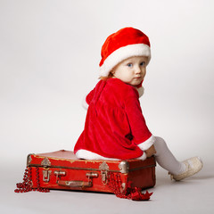 Rear view of girl with Santa cap sitting on suitcase with gifts