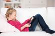 mädchen mit tablet-pc auf dem sofa