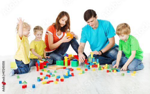 Happy family. Parents with three kids playing blocks over white