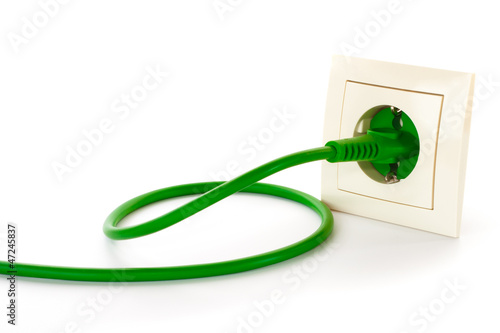 Green power plug into power outlet - 47245837