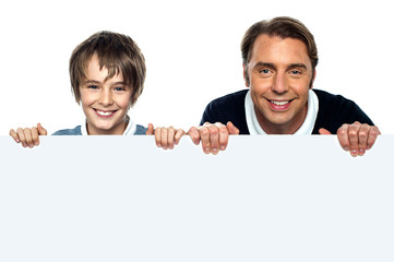 Father and son posing behind big blank banner ad