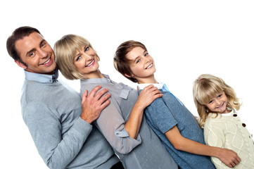 Cheerful family of four leaning backwards