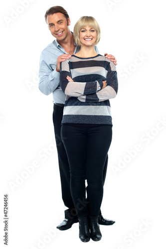 Middle aged husband holding his wife from behind