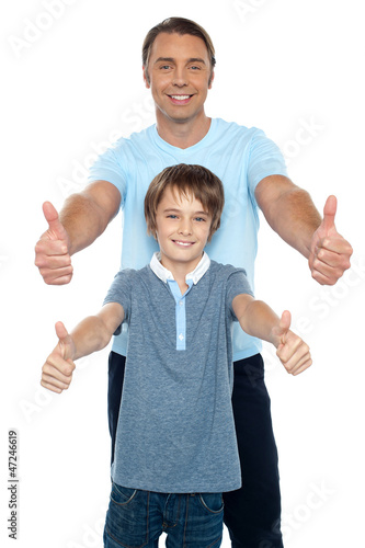 Handsome father and son showing thumbs up to camera