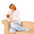 Mother breast-feeding newborn baby on the sofa