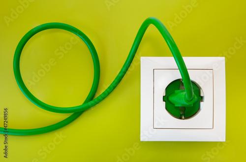 Leinwanddruck Bild Green power plug into white power socket