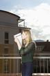 Junge Frau steht auf Balkon und küsst ihren Mietvertrag