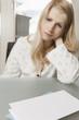 Briefpapier mit Textfreiraum liegt vor Frau mit traurigem Blick