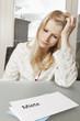 Frau blickt verzweifelt auf Brief mit Mietforderung