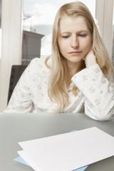 Frau blickt traurig auf Brief mit Textfreiraum