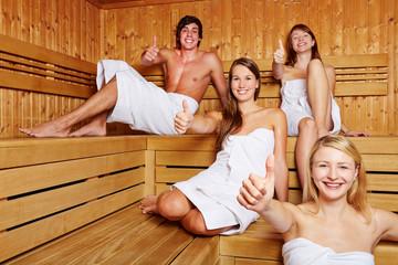 Vier Leute in Sauna halten Daumen hoch