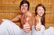 Paar in Sauna hält Daumen hoch