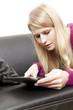 Frau in Freizeitkleidung blickt interessiert auf Tablet PC