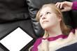 Verträumt blickende Frau auf Couch mit Tablet PC
