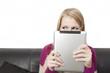 Seitenblick einer Frau die ein Tablet PC vor ihr Gesicht hält