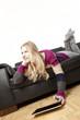 Frau auf Couch mit Tablet PC blicktin die Ferne