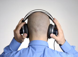 Vista trasera de hombre con audífonos,escuchando música.