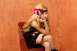 blond fashin kid girl sitting on retro vintage seat