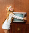Blond vintage 70s kid girl with retro love old tv