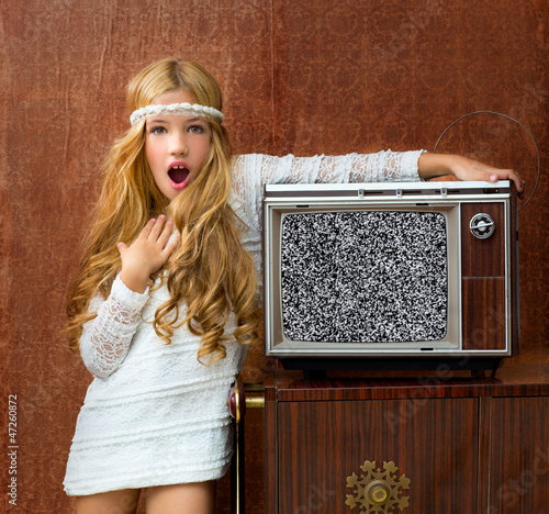 Blond vintage 70s kid girl with retro wood tv surprised