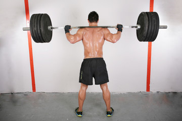 arms and back of a young muscular man working out with a bar