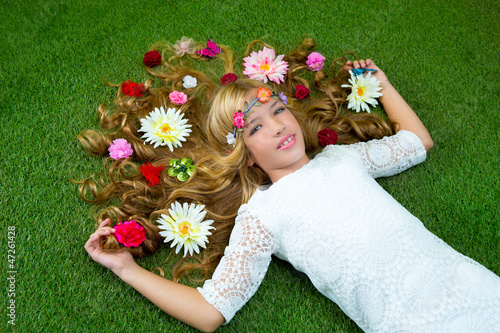 Blond spring girl with flowers on hair over grass