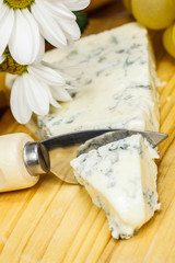Delicious blue cheese with knife and grapes