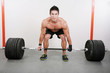 Young and muscular guy holding a barbell.  Crossfit dead lift ex