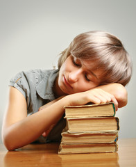 Young woman sleeping on stack of books
