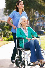 Carer Pushing Senior Woman In Wheelchair