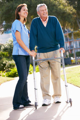 Carer Helping Senior Man With Walking Frame