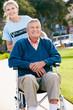 Teenage Volunteer Pushing Senior Man In Wheelchair