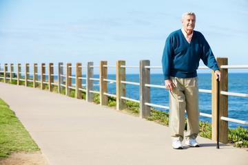 Senior Man Walking Along Path By The Sea