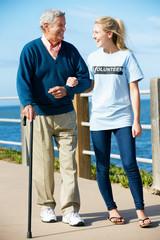 Teenage Volunteer Helping Senior Man Walking Along Path By The S