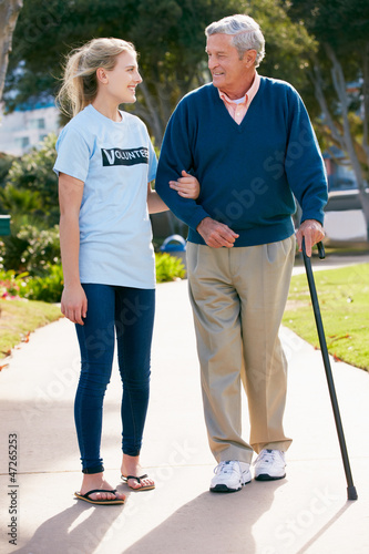 Teenage Volunteer Helping Senior Man Walking Through Park