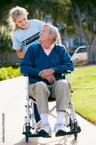 Teenage Volunteer Pushing Senior Man In Wheelchair