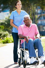 Carer Pushing Unhappy Senior Man In Wheelchair