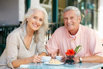 Senior Couple Enjoying Snack At Outdoor Café