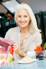 Senior Woman Enjoying Snack At Outdoor Café After Shopping