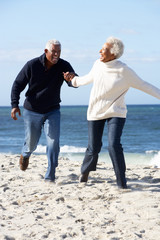 Romantic Senior Couple Running Along Beach