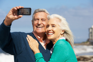 Senior Couple With Camera On Beach
