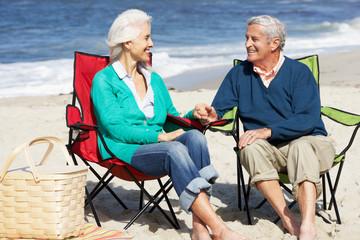 Senior Couple Sitting On Beach In Deckchairs Having Picnic