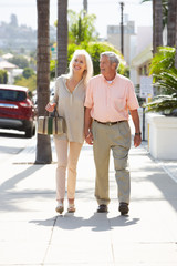 Senior Couple Walking Along Street Together