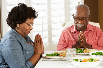 Senior Couple Saying Grace Before Meal At Home