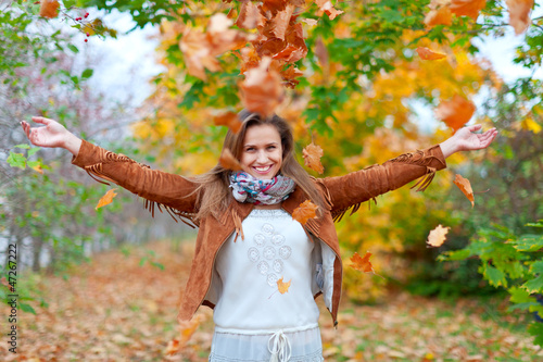 Happy girl throws maple leaves