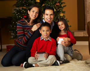 Family In Front Of Christmas Tree