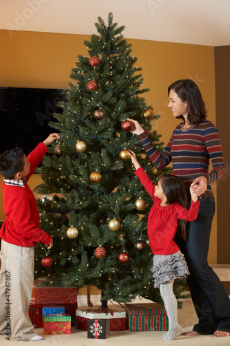 Mother And Children Decorating Christmas Tree